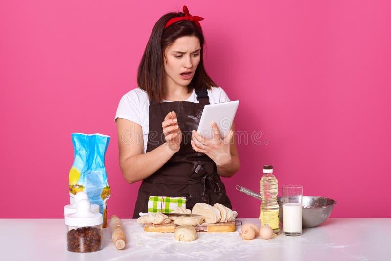 Porträt der emotionalen energischen jungen Frau, die programm auf Tablette kochend, seiend auf der Küche aufpasst und öffnen ihre stockfotos
