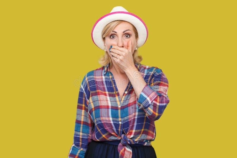 Porträt der entsetzten stilvollen reifen Frau in der zufälligen Art mit Hutstellung, ihren Mund bedeckend und betrachten Kamera m lizenzfreie stockfotos