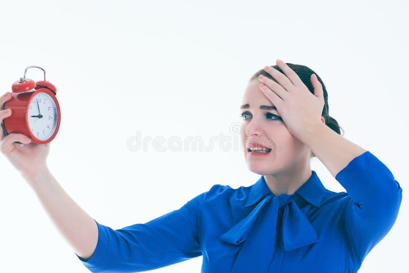 Porträt der entsetzten und verärgerten Frau mit Wecker über weißem Hintergrund lizenzfreies stockbild