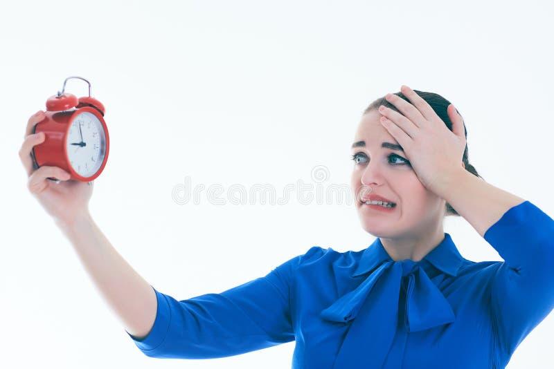 Porträt der entsetzten und verärgerten Frau mit Wecker über weißem Hintergrund stockfotos