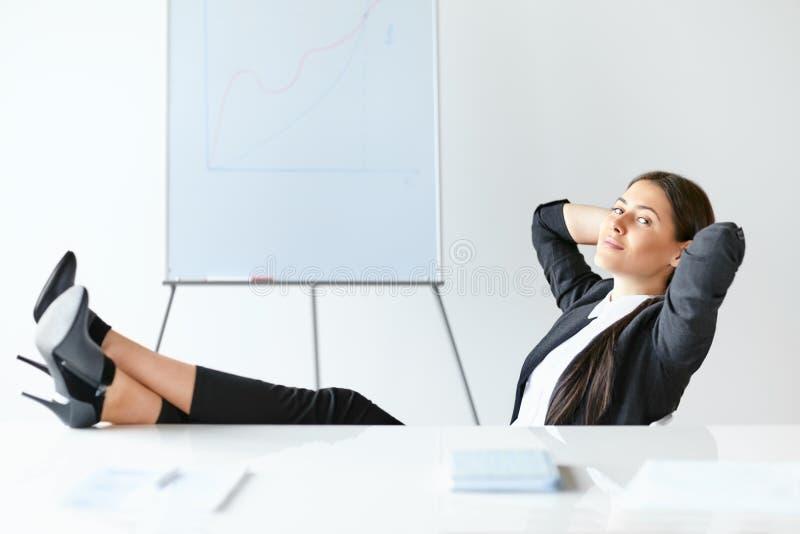 Porträt der entspannten Geschäftsfrau, die mit den Beinen auf Schreibtisch sitzt lizenzfreies stockfoto