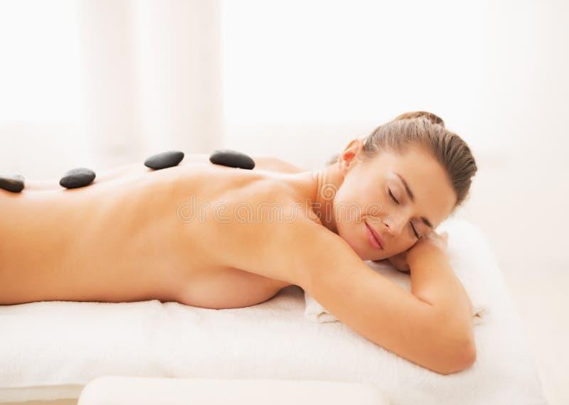Porträt der entspannten jungen Frau, die Warmsteinmassage empfängt lizenzfreie stockfotos