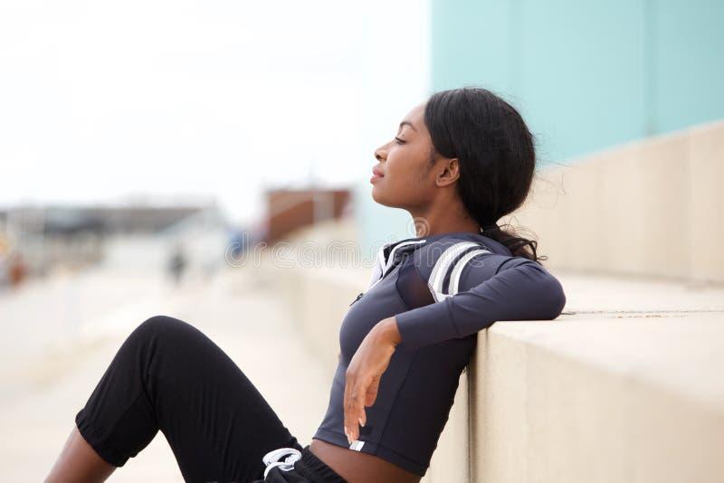 Porträt der Entspannungsaußenseite der geeigneten jungen Afroamerikanersport-Frau stockbilder