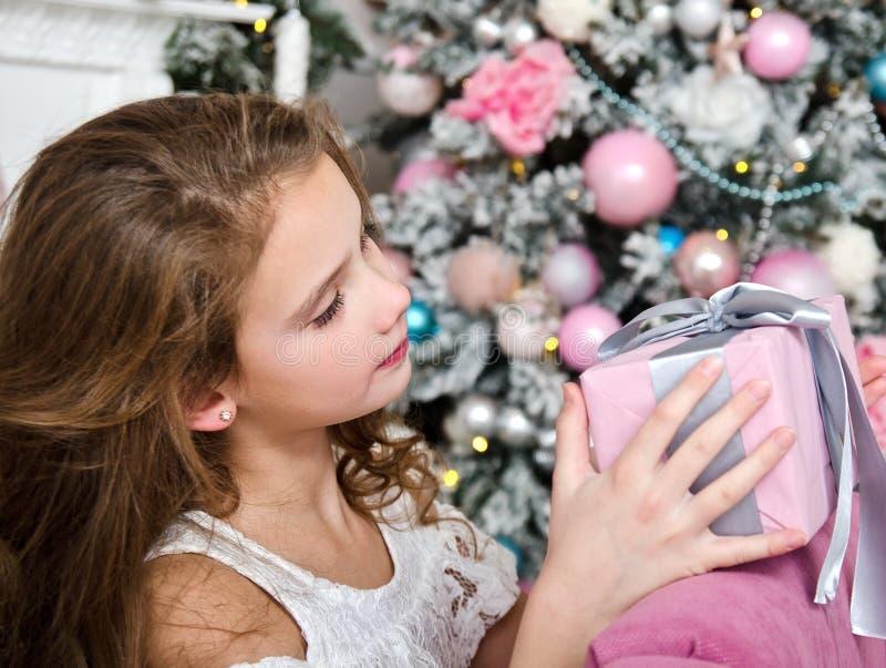 Porträt der entzückenden glücklichen lächelnden Holdinggeschenkbox des kleinen Mädchens Kindernahe Tannenbaum lizenzfreie stockbilder