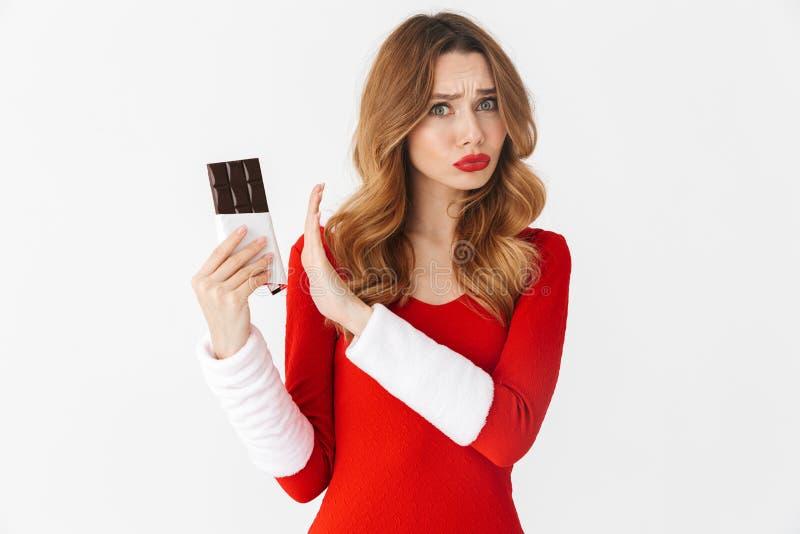 Porträt der ernsten Frau 20s, die rotes Kostüm Santa Clauss hält und zurückweist Schokoriegel, lokalisiert über weißem Hintergrun stockfotografie
