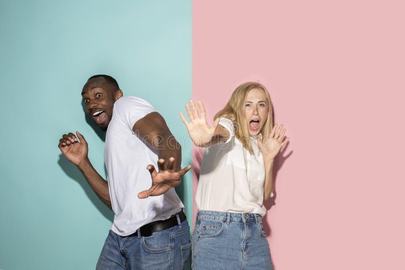 Porträt der erschrockenen Paare auf rosa und blauem Studiohintergrund stockfoto