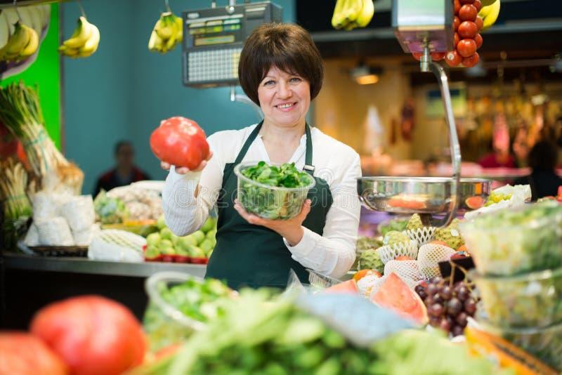 Porträt der erwachsenen Frau Obst und Gemüse verkaufend lizenzfreies stockfoto