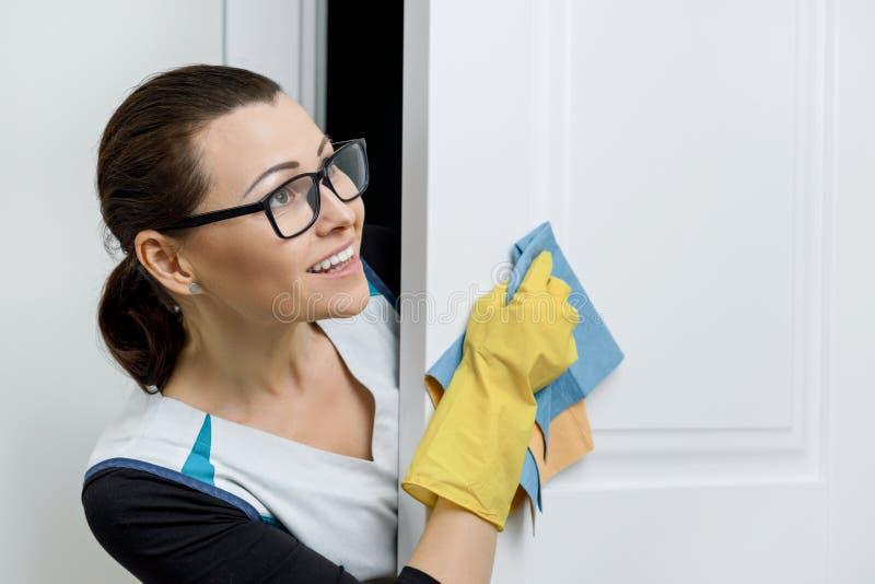 Porträt der erwachsenen positiven lächelnden Frau in den Gläsern und im Schutzblech für Reinigungsgummihandschuhe, weißer Türhint lizenzfreie stockfotografie