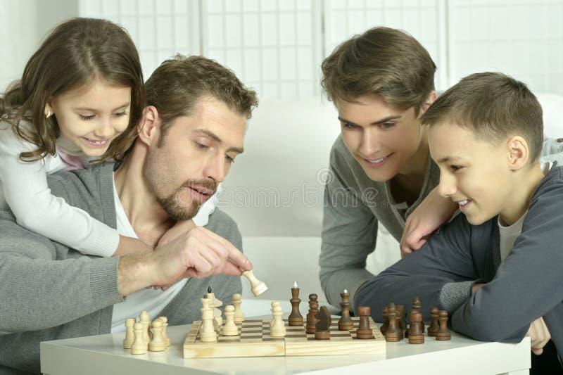 Porträt der Familie Schach zu Hause spielend lizenzfreie stockfotografie