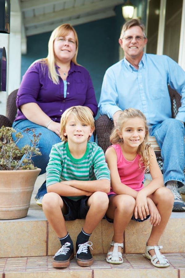 Porträt der Familie sitzend außerhalb des Hauses lizenzfreie stockfotos