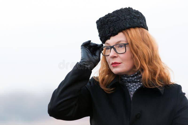 Porträt der Frau in den Gläsern und im schwarzen Mantel Starke rote Haarfrau im Hut Porträt von Geschäftsdame mit den roten Lippe stockbild