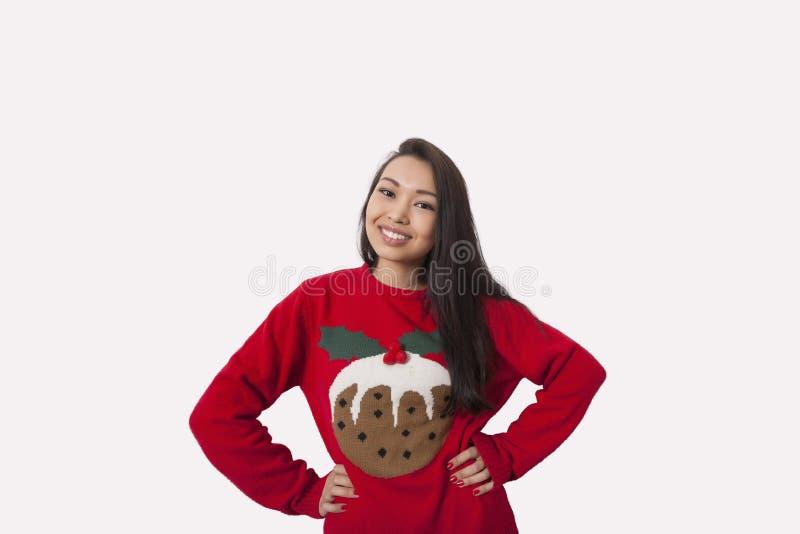 Porträt der Frau in der Weihnachtsstrickjacke, die mit den Händen auf Hüften über grauem Hintergrund steht stockbilder
