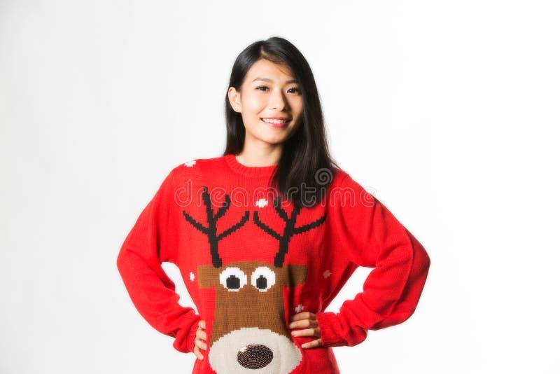 Porträt der Frau in der Weihnachtsstrickjacke, die mit den Händen auf Hüften über grauem Hintergrund steht lizenzfreie stockfotos