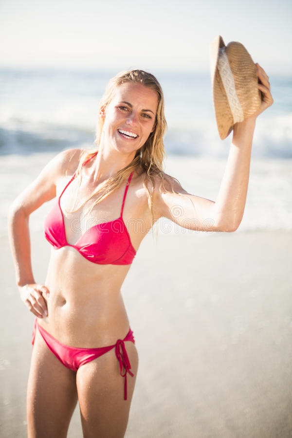 Porträt der Frau im Bikini, der einen Hut auf Strand hält stockbilder