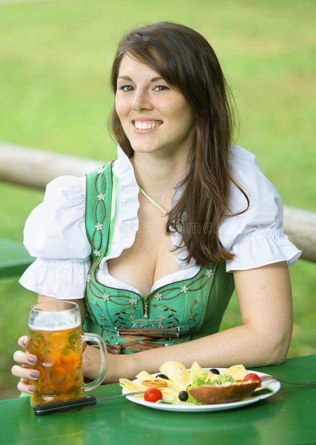Porträt der Frau im Dirndl mit Bier und Lebensmittel stockbild