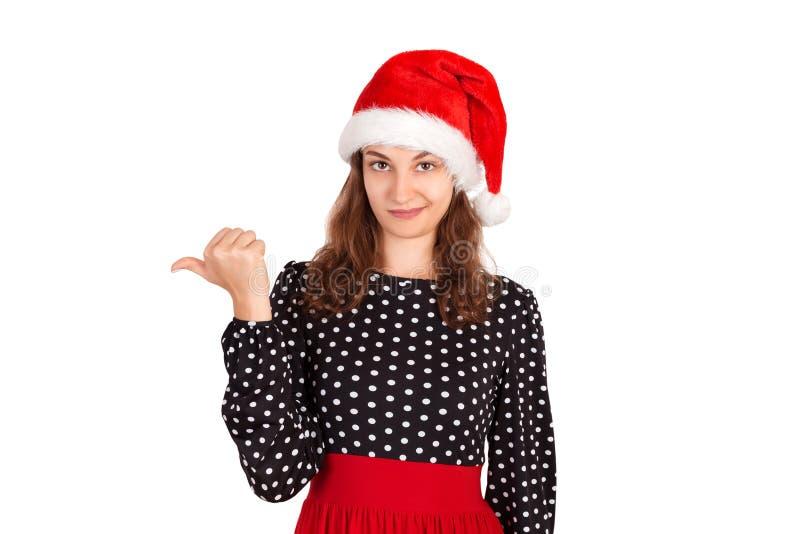 Porträt der Frau im Kleid nach links zeigend mit dem Daumen und Umkippen emotionales Mädchen im Weihnachtsmann-Weihnachtshut loka lizenzfreies stockfoto