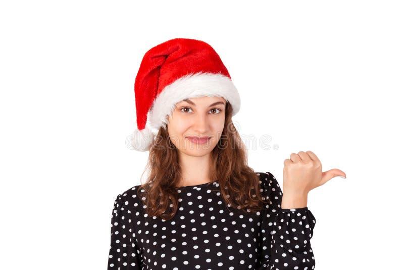 Porträt der Frau im Kleid nach links zeigend mit dem Daumen und verwirrt emotionales Mädchen im Weihnachtsmann-Weihnachtshut loka lizenzfreies stockbild