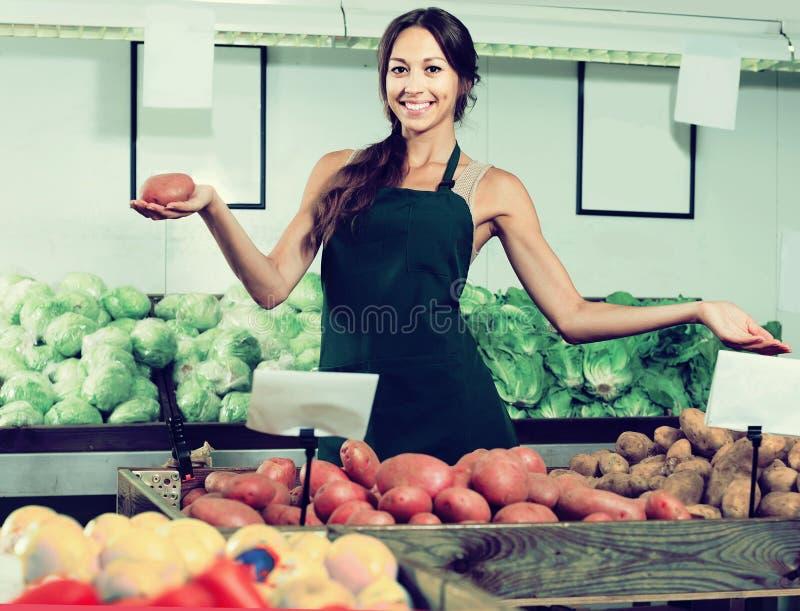 Porträt der Frau im Schutzblech, das organische Kartoffeln im Shop verkauft lizenzfreies stockfoto