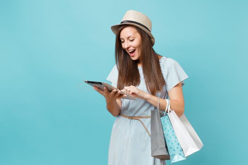 Porträt der Frau im Sommerkleid, Strohhut, der Pakettaschen mit Käufen nach dem on-line-Einkaufen, unter Verwendung des Tabletten lizenzfreie stockfotografie