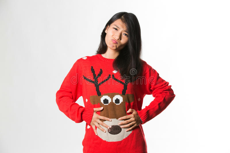 Porträt der Frau im sweatershowing Weihnachten hat sie zu viel Lebensmittel über grauem Hintergrund gegessen stockfotografie