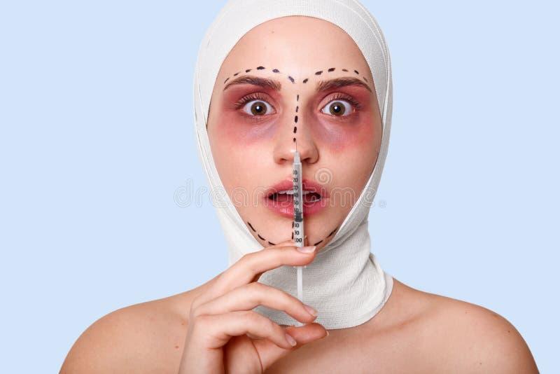 Porträt der Frau in der Klinik mit Verband auf Kopf Dame hält Spritze Dame mit geöffneten Mundblicken erschrocken lokalisiert übe lizenzfreie stockbilder