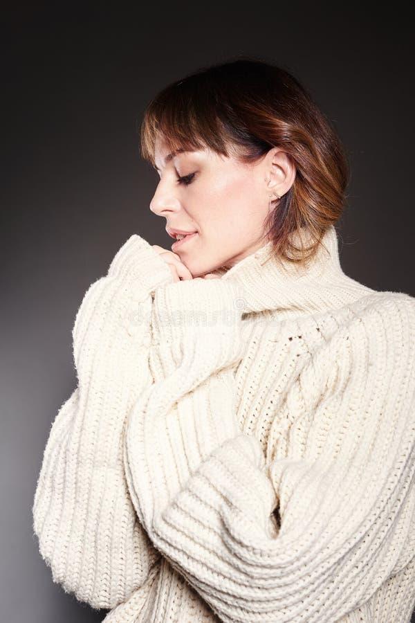 Porträt der Frau mit dem langen Haar glaubt dem kalten Tragen in der weißen Winterstrickjacke, dunkelgrauer Hintergrund lizenzfreies stockbild