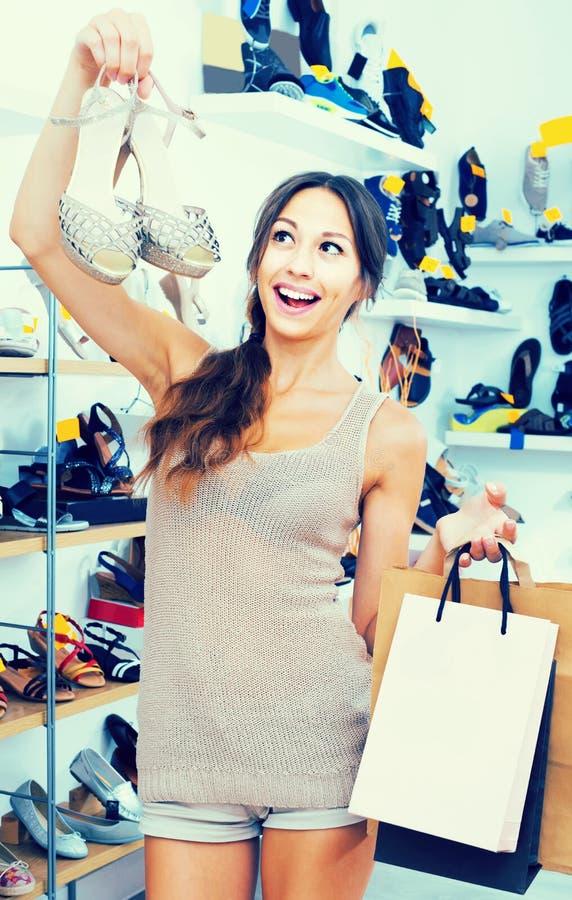Porträt der Frau mit den Einkaufstaschen, die Schuhe in Han ausgewählt werden stockfotos