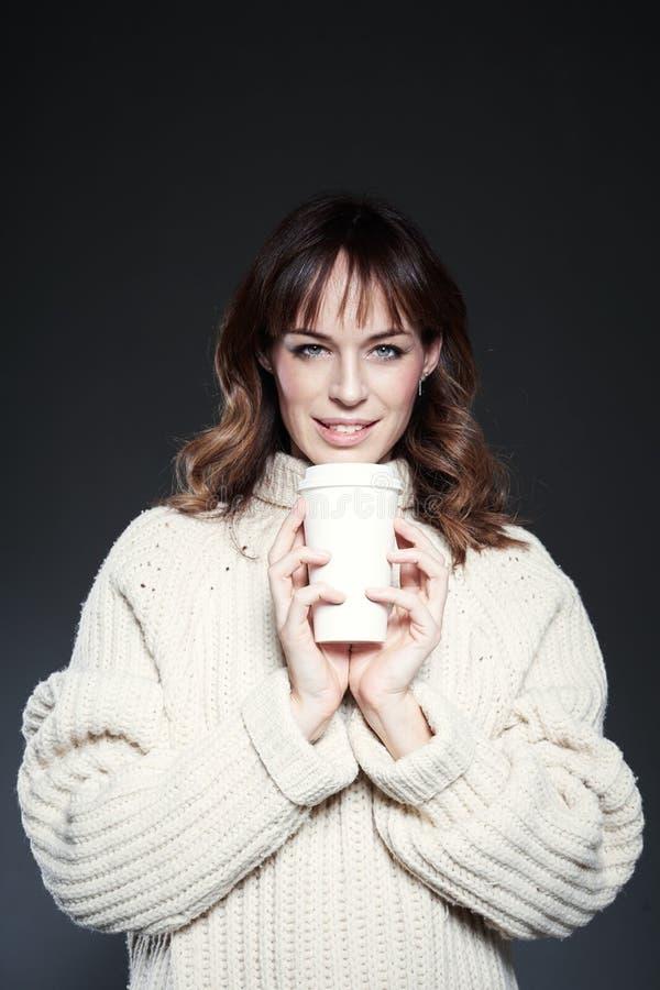 Porträt der Frau mit den geschlossenen Augen, die Strickjacke tragen, hält eine Papierwegwerfkaffeetasse Kaffee trinkend, schauen lizenzfreie stockfotografie