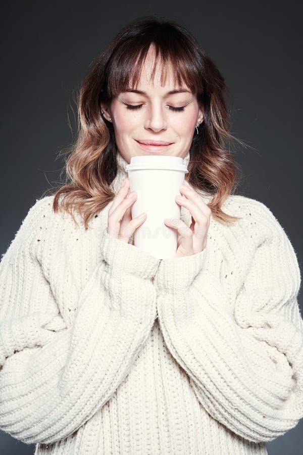 Porträt der Frau mit den geschlossenen Augen, die Strickjacke tragen, hält eine Papierwegwerfkaffeetasse Kaffee trinkend, schauen lizenzfreies stockbild