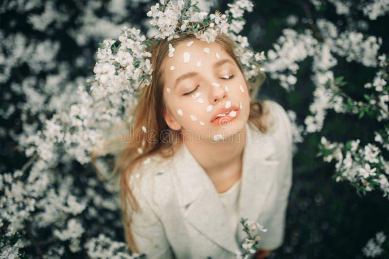 Porträt der Frau mit den Kirschblumenblättern auf ihrem Gesicht unter blühenden Bäumen stockfotos