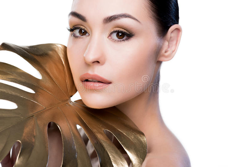 Porträt der Frau mit großem goldenem Blatt nahe dem Gesicht, das Kamera betrachtet lizenzfreie stockbilder