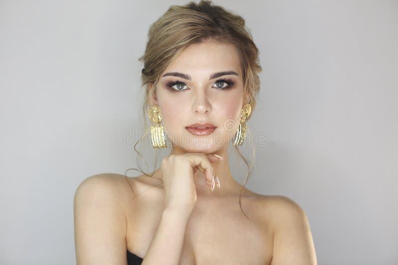 Porträt der Frau mit der Modefrisur und -make-up, die große goldene Ohrringe tragen stockbild