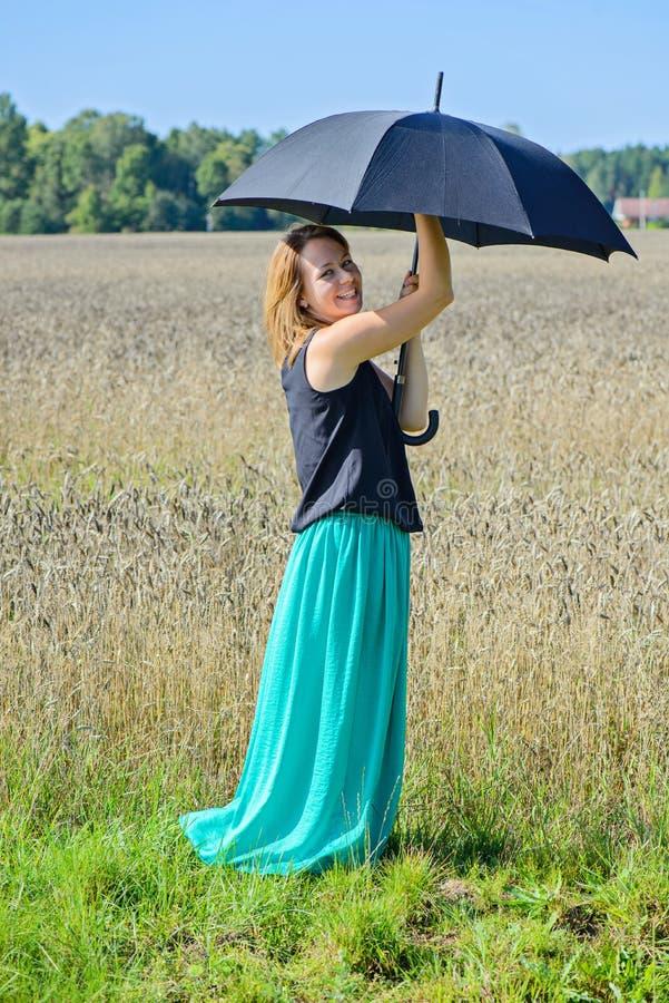 Porträt der Frau mit Regenschirm auf dem Gebiet stockfotos