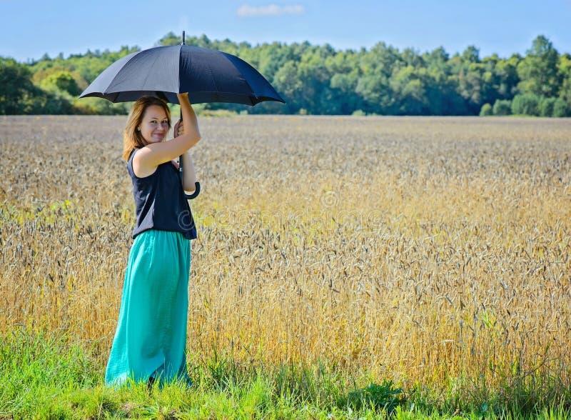 Porträt der Frau mit Regenschirm auf dem Gebiet stockfotografie