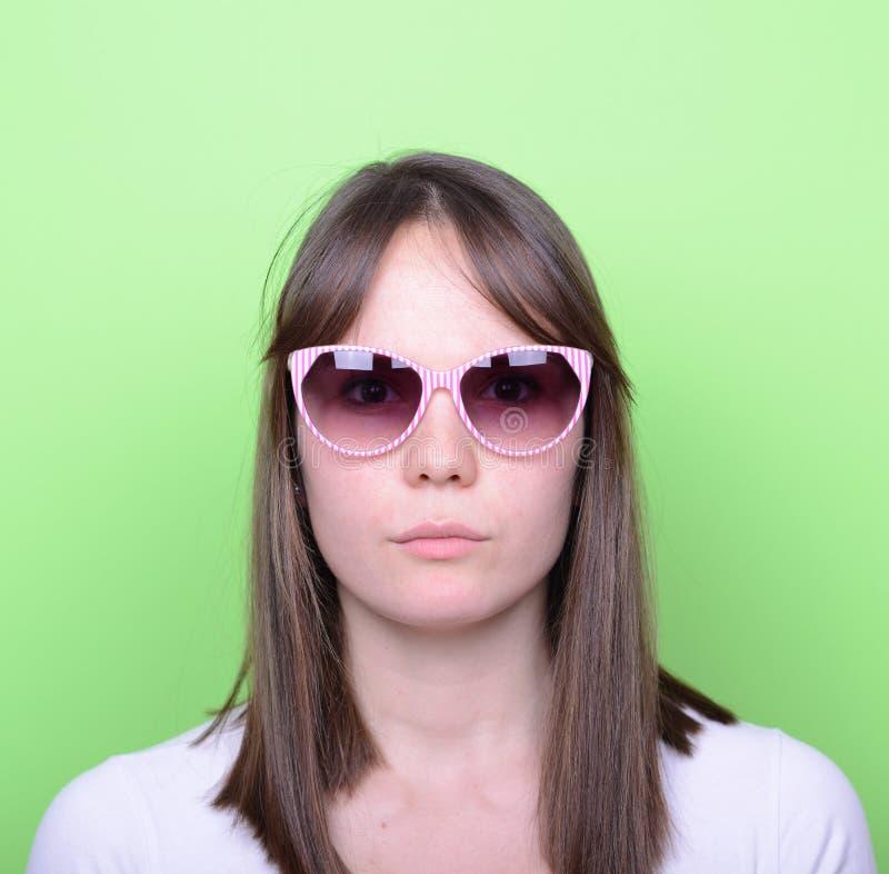 Porträt der Frau mit Retro- Gläsern gegen grünen Hintergrund lizenzfreie stockfotos