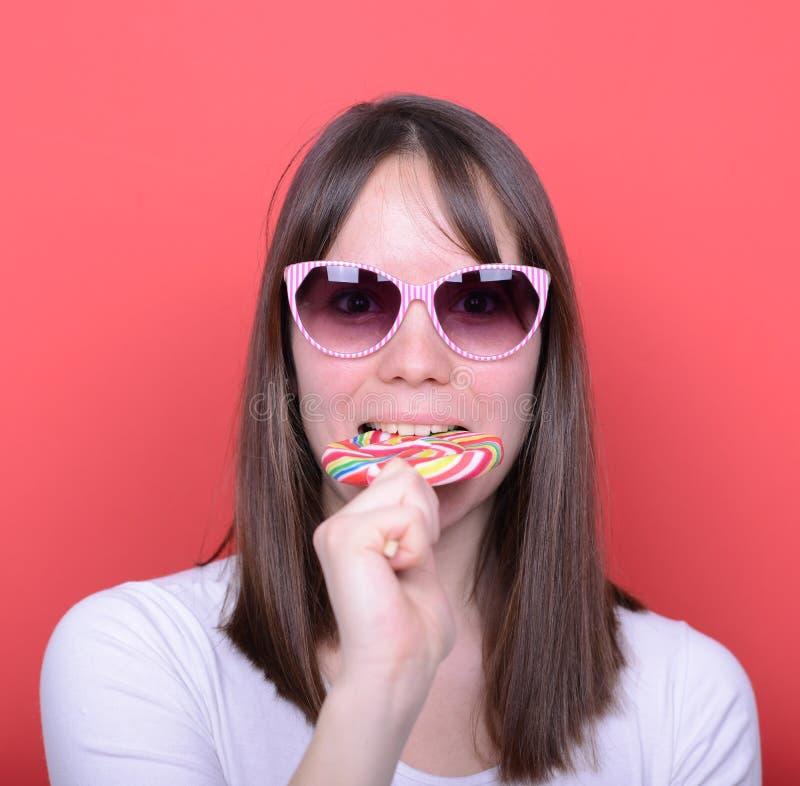 Porträt der Frau mit Retro- Gläsern und Lutscher gegen rotes Ba lizenzfreie stockbilder