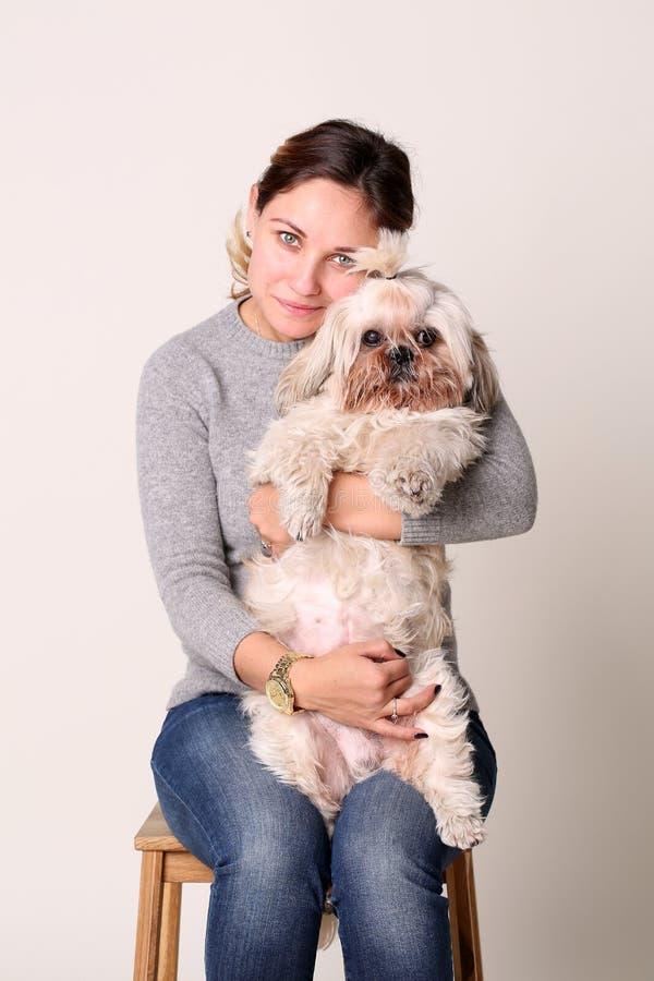 Porträt der Frau mit shih-tzu Hund, sitzend auf Stuhl im Studio stockfotografie
