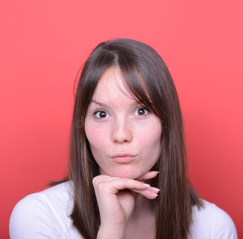 Porträt der Frau mit sinnlichem Blick gegen roten Hintergrund stockfotos