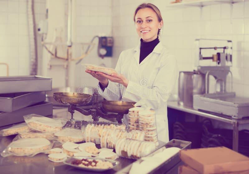 Porträt der Frau mit Verpackung von turron in der Lebensmittelfabrik stockfotografie