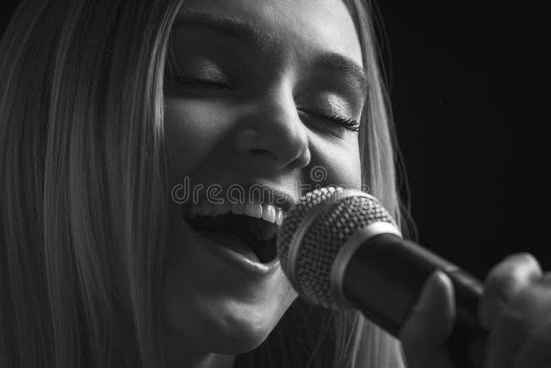Porträt der Frau singend in das Mikrofonlied lizenzfreie stockbilder