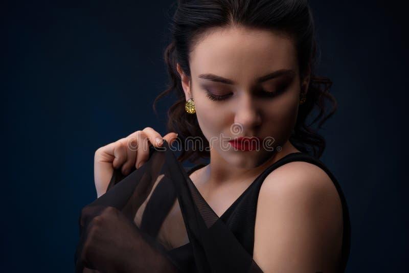 Porträt der Frau unten schauend mit Stück von Tulle lizenzfreie stockbilder