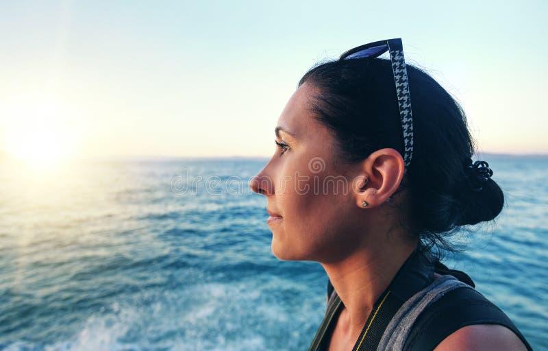 Porträt der Frauennahaufnahme auf dem Hintergrund des Meeres und Sonnenuntergang an einem Sommerabend lizenzfreie stockfotografie