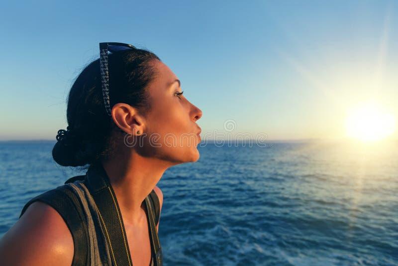 Porträt der Frauennahaufnahme auf dem Hintergrund des Meeres und Sonnenuntergang an einem Sommerabend stockfotografie
