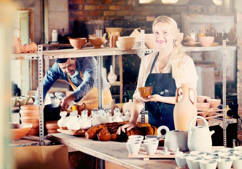 Porträt der frohen Frauentonwarenarbeitskraft mit keramischer Tonware lizenzfreie stockbilder