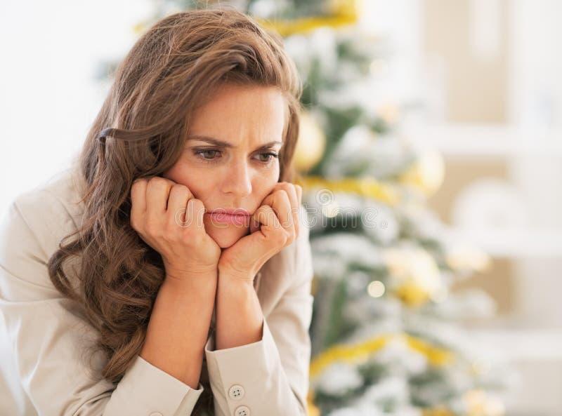 Porträt der frustrierten jungen Frau nahe Weihnachtsbaum lizenzfreie stockfotografie