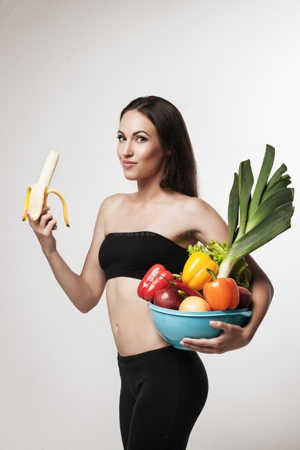 Porträt der geeigneten Frau der Junge, die Obst und Gemüse hält stockfoto