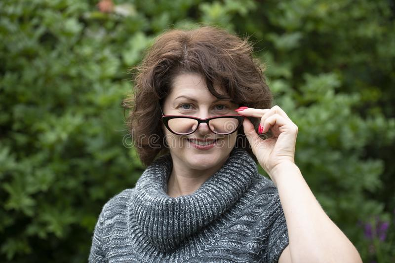 Porträt der gelockten Frau in den roten Gläsern auf Natur stockbilder