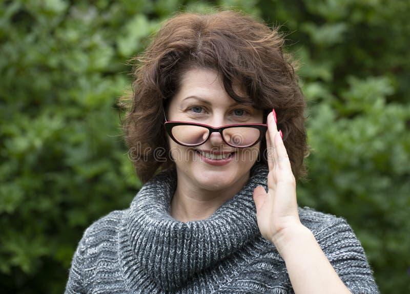 Porträt der gelockten Frau in den roten Gläsern auf Natur stockfotos