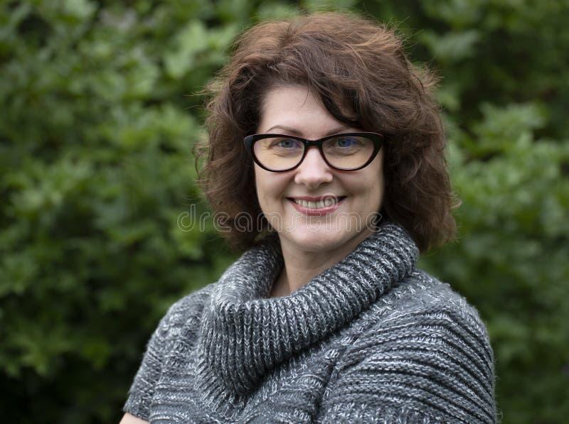 Porträt der gelockten Frau in den roten Gläsern auf Natur lizenzfreies stockfoto