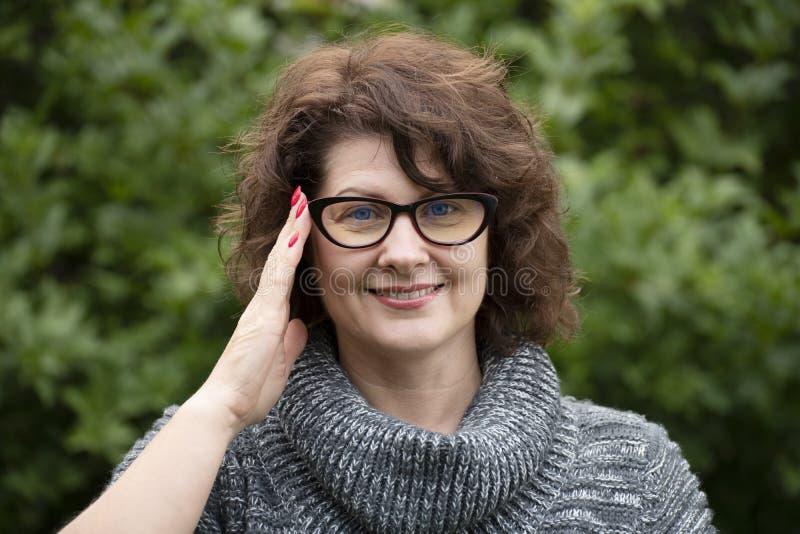 Porträt der gelockten Frau in den roten Gläsern auf Natur lizenzfreie stockfotografie